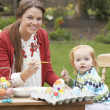 Stock Photo: Mother And Daughter Painting Easter Eggs In Gardens