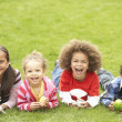 Foto Stock: Group Of Children Laying On Grass With Easter Eggs