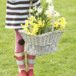 Stock Photo: Detail Of Girl Holding Basket Of Daffodils In Garden