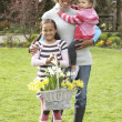Mother And Children Holding Basket Of Daffodils In Garden — Stock Photo