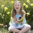 Girl Eating Chocolate Egg On Easter Egg Hunt In Daffodil Field — Stock Photo
