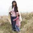 Mother And Daughter Wrapped In Blanket Amongst Dunes On Winter B - Stock Photo