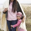 Mother And Daughter Wrapped In Blanket Amongst Dunes On Winter B - Foto Stock