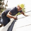 Stock Photo: Roofer Working On Exterior Of New Home