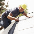 Roofer Working On Exterior Of New Home - Stockfoto