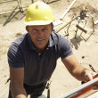 construction worker climbing ladder on building site for new hom — Stock Photo