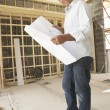 Foto Stock: Architect With Plans In New Home