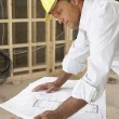 Architect Studying Plans In New Home — Stok fotoğraf