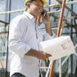 Architect With Plans Outside New Home Talking On Mobile Phone — Foto Stock