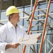 Architect Studying Plans Outside New Home — Stock Photo #4842549