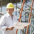 Architect Studying Plans Outside New Home - Foto Stock