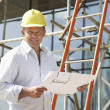 Architect Studying Plans Outside New Home — Stock Photo #4842552