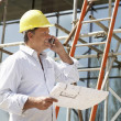Architect With Plans Outside New Home Talking On Mobile Phone - 