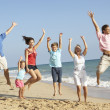 Portrait Of Three Generation Family On Beach Holiday Jumping In - Stock Photo