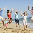 Portrait Of Three Generation Family On Beach Holiday Jumping In — Stock Photo