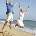 空気中のジャンプ ビーチ休日を楽しんでいる年配のカップル — ストック写真