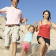 Family Enjoying Beach Holiday Running Down Dune — Stock Photo #4842640