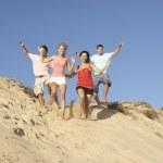 Group Of Friends Enjoying Beach Holiday Running Down Dunes — Stock Photo