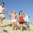 Group Of Friends Enjoying Beach Holiday Running Down Dunes — Stock Photo #4842663