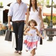 Young Family Enjoying Shopping Trip Together - Stockfoto