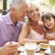 Grandparents With Granddaughter Enjoying Coffee And Cake In Caf — Stock Photo #4842802