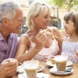 Grandparents With Granddaughter Enjoying Coffee And Cake In Caf — Stock Photo #4842805