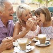 Grandparents With Granddaughter Enjoying Coffee And Cake In Caf — Stock Photo