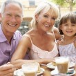 Stock Photo: Grandparents With Granddaughter Enjoying Coffee And Cake In Caf