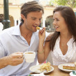Young Couple Enjoying Coffee And Cake In Caf — Stockfoto