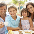 young family enjoying cup of coffee and cake in caf — Stock Photo #4842831