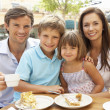 Young Family Enjoying Cup Of Coffee And Cake In Caf — Stock Photo #4842832