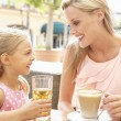 Mother And Daughter Enjoying Cup Of Coffee And Juice In Caf — Stock Photo #4842860