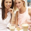 Two Young Women Enjoying Cup Of Coffee In Caf — Stock Photo #4842883