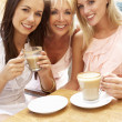 Three Women Enjoying Cup Of Coffee In Caf — Stock Photo