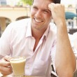 Young Man Enjoying Cup Of Coffee In Caf - Stock Photo