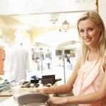 kobieta asystent sprzedaży w kasie odzież sklep — Zdjęcie stockowe