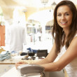 Female Sales Assistant At Checkout Of Clothing Store — Foto de Stock