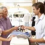 Asystent sprzedaży mężczyzna w kasie odzież sklep z klientem — Zdjęcie stockowe