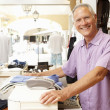 Male Sales Assistant At Checkout Of Clothing Store — Stockfoto