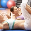 Women Doing Stretching Exercises In Gym — Stock Photo #4842903