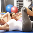Foto de Stock  : Women Doing Stretching Exercises In Gym