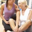 Stock Photo: WomDoing Stretching Exercises In Gym With Trainer