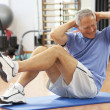 Stock Photo: Senior Man Doing Sit Ups In Gym