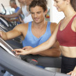Woman Working With Personal Trainer On Running Machine In Gym — Stock Photo #4842995