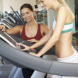 Woman Working With Female Personal Trainer On Running Machine In - Stock Photo