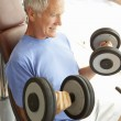 Stock Photo: Senior Man Working With Weights In Gym