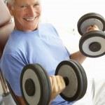 Senior hombre trabajando con pesas en el gimnasio — Foto de Stock