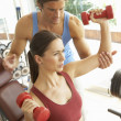 Young Woman Working With Weights In Gym With Personal Trainer - Zdjęcie stockowe