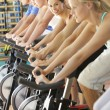 Stock Photo: Woman Cycling In Spinning Class In Gym