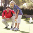 Stock Photo: Father Teaching Son To Play Golf On Putting On Green